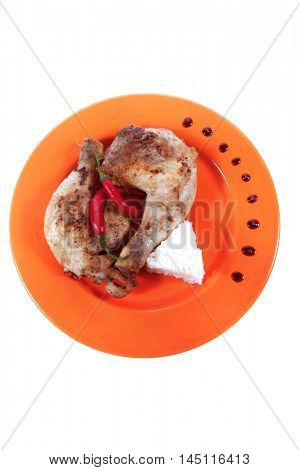 grilled chicken thighs on orange plate with white rice and red hot chili pepper isolated over white background