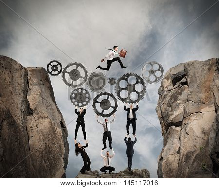 Business people support a gear mechanism for passing a man in the mountains