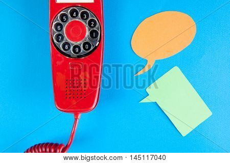 Vintage red phone and speech ballons on blue background
