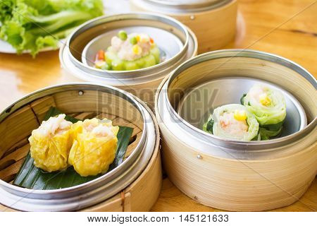 baskets of dimsum - chinese steamed food in bamboo basket