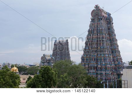 Madurai India - October 19 2013: The North and West Gopuram of the Meenakshi temple is shot from the North. Golden dome of goddess shrine and green trees in photo.