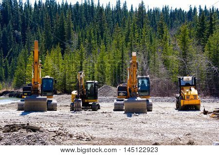 Line up of earth moving machines during construction in the forest