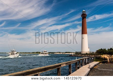 Fishing boats heading out to sea through Barnegat Inlet with Barnegat Lighthouse in background