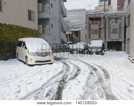 Tokyo Japan - February 9 2014: snow covering cars parked after blizzard in tokyo