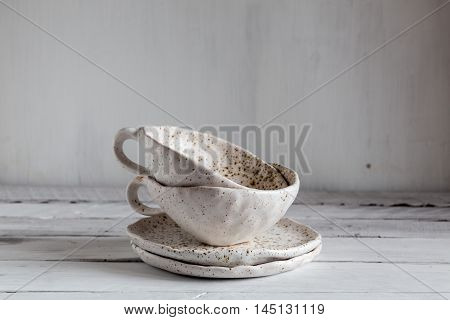 set of white pottery on a white background white pottery in brown speckled plates and cups from clay