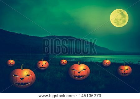 Mountain and beautiful full moon outdoors at night. Pumpkins with scary face on the riverbank. Vintage green background for Halloween holiday. The moon were NOT furnished by NASA.