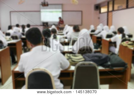 Blur Image students sitting in a lecture room with the teacher in front of the class with white projector slide screen