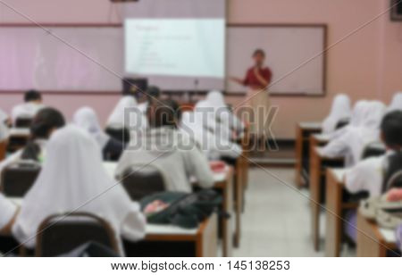 students sitting in a lecture room with the teacher in front of the class with white projector slide screen : Blur blurred  of view from back of the classroom.