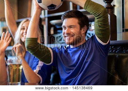 people, leisure, soccer and sport concept - happy football fans or friends with beer and ball celebrating victory at bar or pub