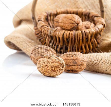 Garden walnuts in a wicker basket on white background.