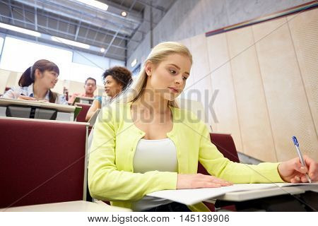 education, high school, university, learning and people concept - student girl writing to notebook at lecture hall