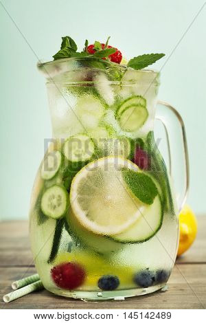 Infused water with cucumber, lemon, lime, berry and mint on blue background