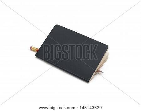Black paperback notebook with a pencil between the sheets.