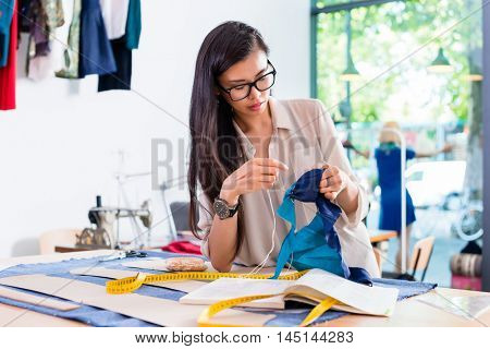 Asian fashion designer woman sewing in her workshop