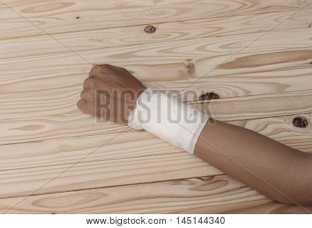 Gauze bandage the hand contusion. treating with a wrist left male  is wrapping his injury on a wooden table .