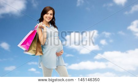 pregnancy, sale, motherhood, people and expectation concept - happy pregnant woman with shopping bags touching her big belly over blue sky and clouds background