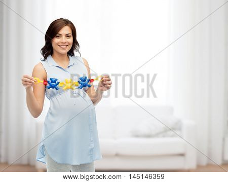 pregnancy, motherhood, people and expectation concept - happy pregnant woman holding rattle toy over home living room background