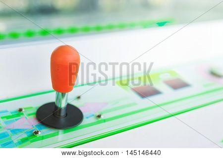 Vintage arcade video game joystick in amusement park selective focus