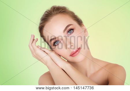 beauty, people and bodycare concept -beautiful young woman face and hands over green background