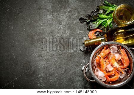 White wine with shrimp and ice. On a stone background.