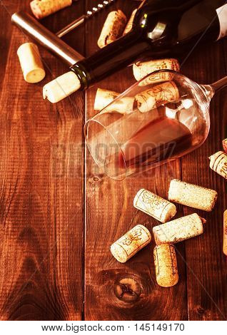 Bottle of red wine, glass, corks and corkscrew   over rustic wooden table background