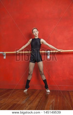 Ballerina Performing At Barre Against Red Wall