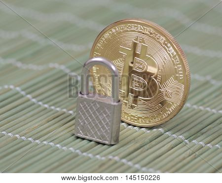 Gold-plated Bitcoin and padlock on a wooden tablecloth. Selective focus.