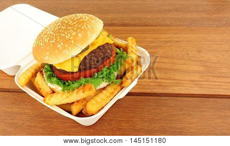 Cheeseburger and fries in a take away box on a wood background