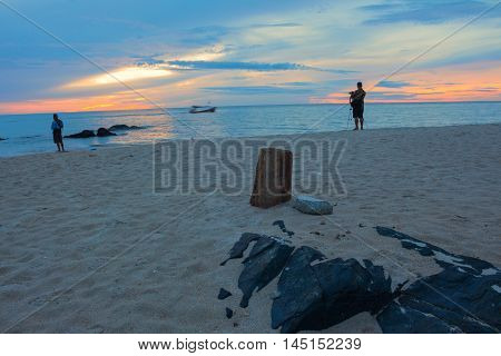 Sunrise morning time before cameraman a fisherman on the beach. beautiful Colorful sky and water in lake reflected. Select focus with shallow depth of field . with copy space.