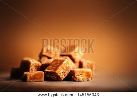 Toffees. Caramel pieces with copy space for your design over dark wooden background. Golden Butterscotch toffee caramel