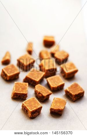Toffees. Caramel pieces with copy space for your design over white background. Golden Butterscotch toffee caramel