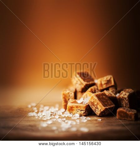 Toffees. Salted caramel pieces and sea salt close up top view. Butterscotch toffee caramel with copyspace for text