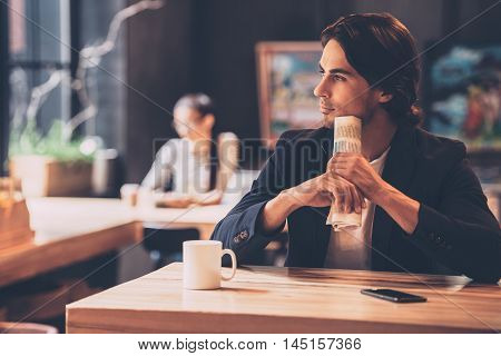 Lost in thoughts. Handsome young man holding newspaper and looking thoughtful while sitting in cafe