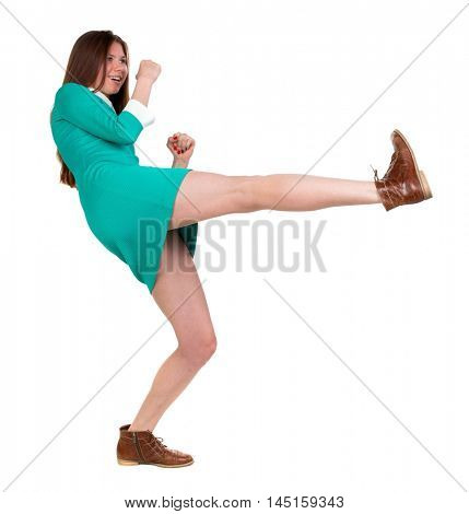 skinny woman funny fights waving his arms and legs. Long-haired brunette in a green dress fights feet.