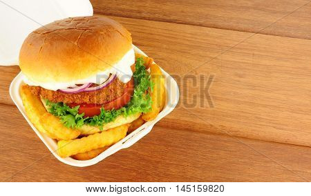 Chicken sandwich and fries in a take away box on a wood background