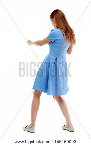 back view of standing girl pulling a rope from the top or cling to something. Isolated over white background. Skinny girl in a blue dress and pulls the load on the rope.