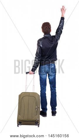 Back view of man with green suitcase man greeting waving from his hands. Tourist holding the handle of a suitcase on wheels. Traveler waving his hand good-bye.