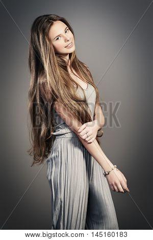 Beautiful girl with shiny long hair smiling at camera. Healthy hair, haircare.Studio shot over grey background.