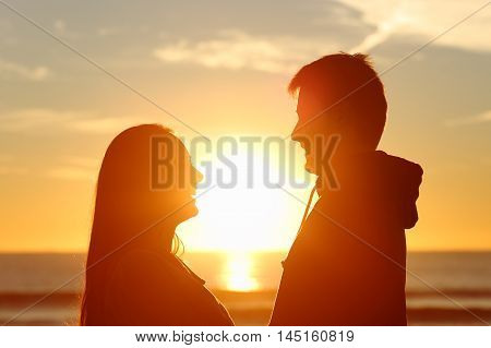 Couple standing looking each other and falling in love with the sun in the middle at sunset in the beach
