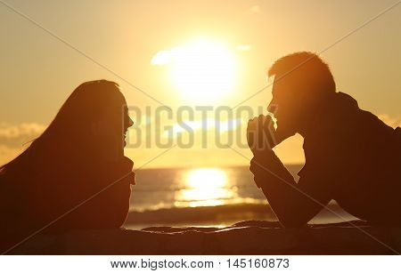 Profile of a couple silhouette looking each other at sunset on the beach with the sun in the middle and a warmth light