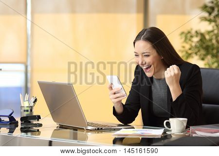 Excited businesswoman winning after achievement reading a smart phone sitting in a desktop at office
