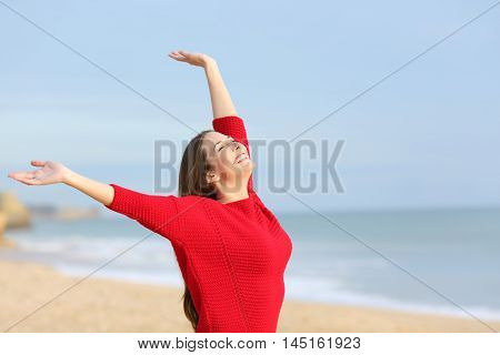 Portrait of a happy joyful woman excited and raising arms wearing a red sweater in the beach in a sunny morning