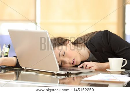 Overworked and tired businesswoman sleeping over a laptop in a desk at work in her office