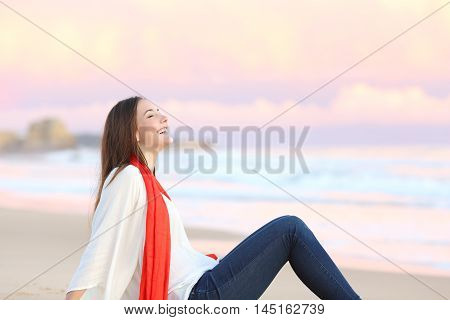 Side view of a happy woman sitting on the sand of the beach breathing fresh air at sunset with the ocean and a warmth pink sky in the background
