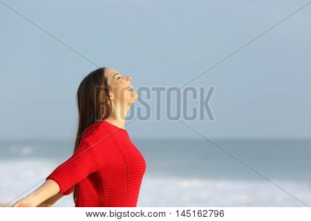 Side view of a happy excited woman wearing red sweater breathing fresh air on the beach with the horizon in the background