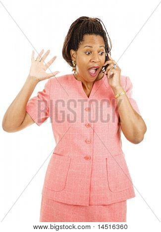 Beautiful african american woman gets exciting news over her mobile phone.  Isolated on white.
