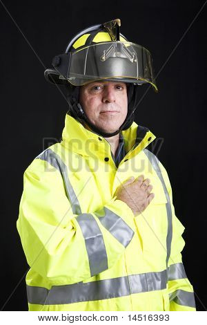 Firefighter says the Pledge of Allegiance with his hand on his heart.  Black background.