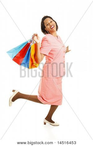 Happy african-american woman skipping along with her shoppping bags.  Full body isolated on white.