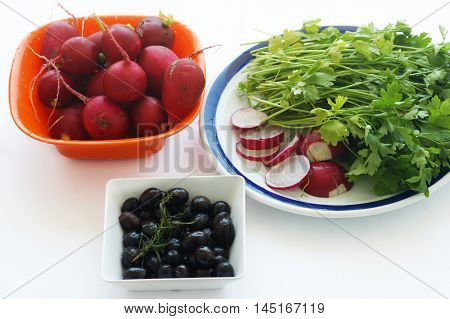 Olives, radishes and parsley in the toes on the white background