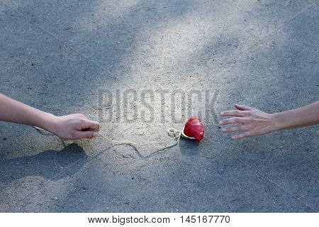 the lure of the red purse tied to a rope on the background of asphalt road / bad business